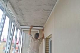 Мастер устанавливает ПВХ панели на потолок